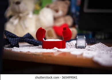 Wedding rings in gift box, bow and watch on background. Shallow depth of field