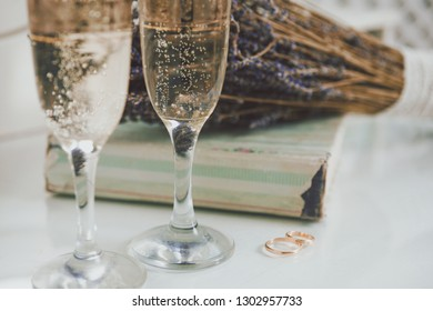 Wedding rings, glasses of champagne, a bouquet of dry lavender on a white background