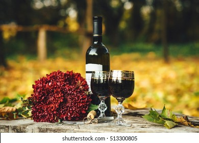 Wedding rings, glasses of wine, a bouquet of flowers on a wooden board.