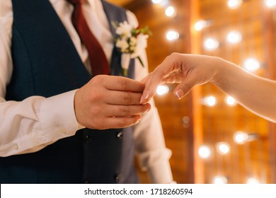 Wedding rings in the hands of the bride and groom. Wearing wedding rings, gentle touches, hands of the bride.