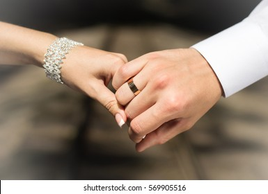 Wedding rings in the hands of lovers. Husband and wife holding hands. Golden decoration. Celebration. Happiness