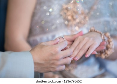 Wedding rings. He Put the Wedding Ring on Her. Close up Groom Put the Ring on bride. thai wedding ceremony and thai wedding decoration.