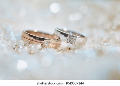 Wedding rings, jewelry and symbols attributes taken with selective focus. Holiday, celebration. Macro. Blur. Bridal bouquet on background