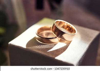 wedding rings lie on the box near a wedding bouquet