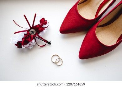 Wedding rings lie on a white table with red shoes of the bride