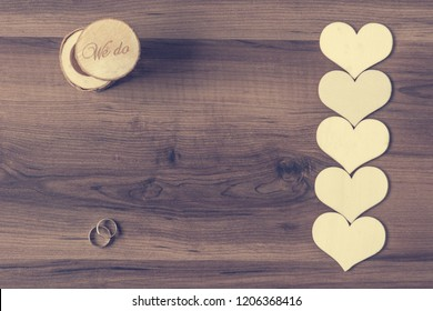 corrugated kraft paper texture wedding rings with line of hearts on wooden desk and a box
