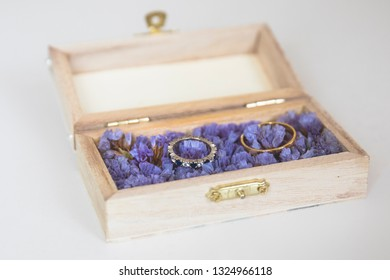 wedding rings in a little wooden box presented on purple flowers
