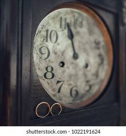 wedding rings lying on vintage wooden clock