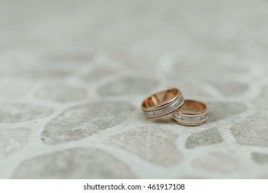 Wedding rings made of white and yellow gold lie on the pavement