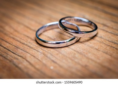 Wedding rings  layingon natural wooden table or desk. Bride and Grooms silver or white gold weddingrings on natural wooden surface. Close up photo.