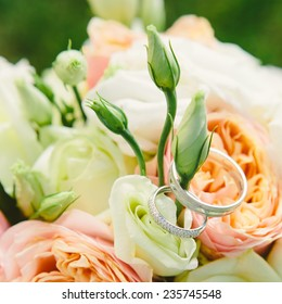 Wedding Rings Nestled in Wedding bouquet. Warm colors. Shallow dof.