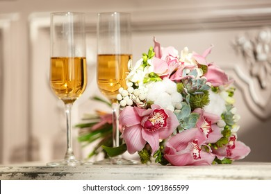 Wedding rings on a beautiful bouquet and glasses with wine