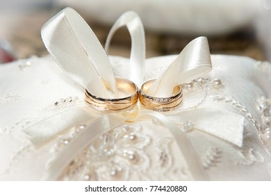Wedding rings on a beautiful pillow with ribbon