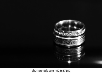 Wedding rings on a black glossy background, mirror image
