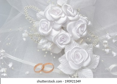 Wedding rings on bridal veil with white boutonniere on gray background
