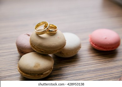 Wedding rings on the colorful macarons
