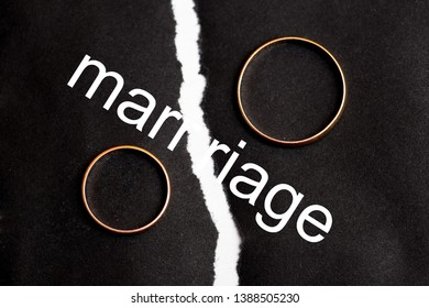 Wedding rings on different halves of a torn sheet of paper. Broken word marriage