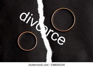 Wedding rings on different halves of a torn sheet of black paper. Broken word divorce