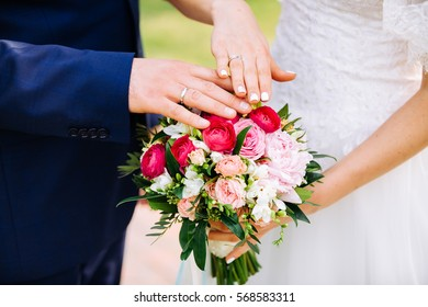 wedding rings on the fingers of the bride and groom, bride holding a wedding bouquet