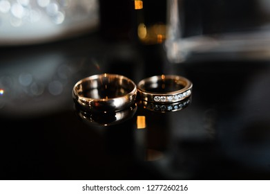 wedding rings on glass, black background, close up