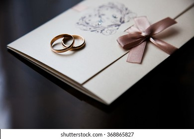 Wedding rings on the invitation card, rings on a dark background, preparations for the wedding, wedding decorations