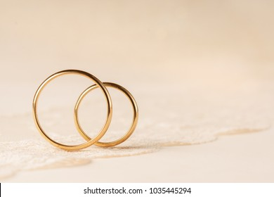 Wedding rings on lace creamy background.