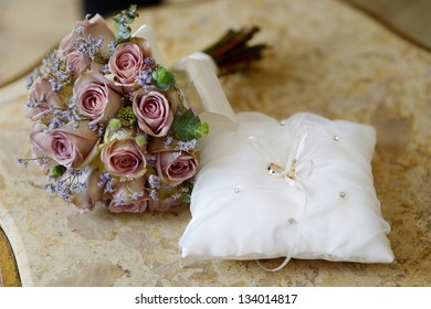 Wedding rings on a pillow and a bouquet