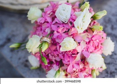 Wedding rings on pink bouquet