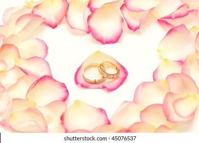 Wedding rings on a red rose petal