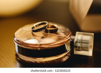 Wedding rings on the table with a bottle of perfume