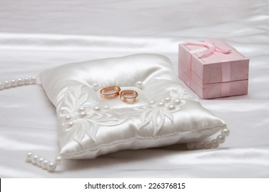 The wedding rings on a white satin pillow