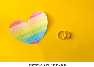 Wedding rings on a yellow background and a heart in the form of a flag lgbt, same-sex marriage, homosexuality
