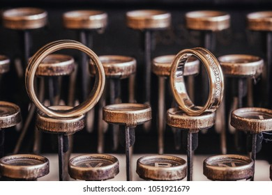 Wedding rings placed on an ancient typewriter letter buttons.