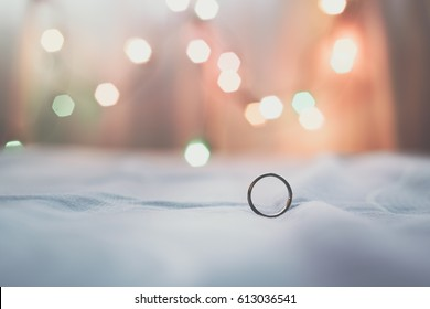 Wedding rings placed on a bed
