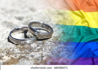 Wedding rings with rainbow flag on a stone