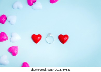 Wedding rings and red heart and copyspace for text on blue background, love and Valentines Day concept.