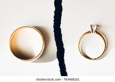 Wedding rings separated by a dark crack. Symbolizing a broken marriage.