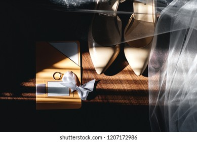 Wedding rings and shoes of the bride with a wedding card