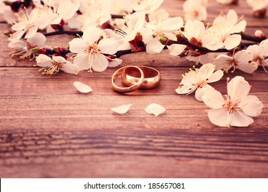 Wedding rings. Spring. Flowering branch with white delicate flowers on  wooden surface. Declaration of love, two hearts, couple. Wedding invitation space for text