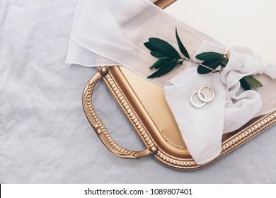 Wedding rings. Wedding symbols, attributes. Holiday celebration. Items on a gold  tray.