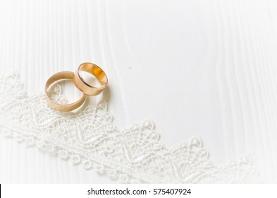 Wedding rings and white lace ribbon on the wooden background