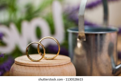 Wedding rings and white rose on lace light background