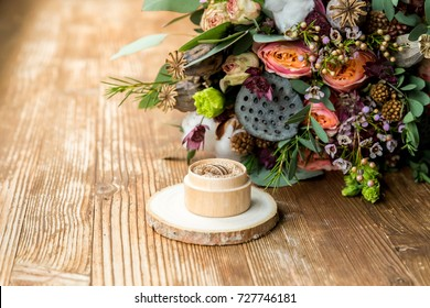 Wedding rings in the wooden box with fall bridal bouquet