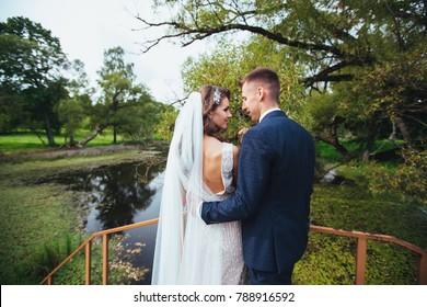 Wedding romantic couple in park in wedding day . Groom hugging bride outdoor