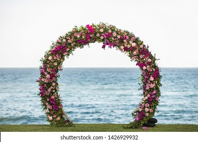 Wedding round arch decorated with beautiful colorful orchid and rose flowers on the beach. Ocean on background.