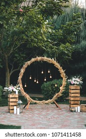 Wedding round arch in rustic style decorated with grass hay field color and retro light bulbs. Near wooden boxes with flower bouquets and candles