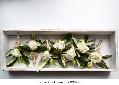 Wedding set of boutonnieres of roses in a wooden box.