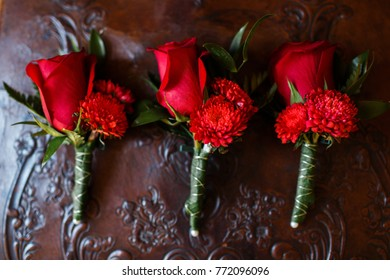 Wedding set of three boutonnieres of red roses on a leather chair.