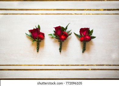 Wedding set of three boutonnieres of red roses on the table.