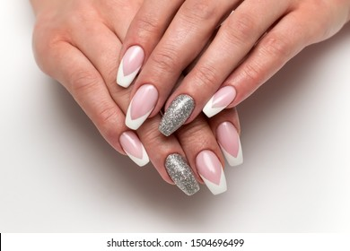 Wedding sharp French manicure with silver sequins on the ring fingers on a white background close-up on long nails
